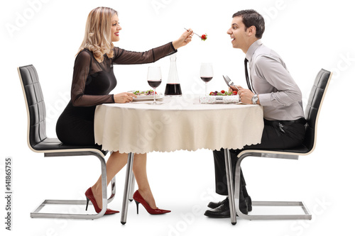 Photo  Young woman feeding her boyfriend salad at restaurant table