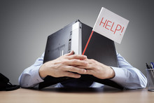 Businessman Burying His Head Uner A Laptop Asking For Help