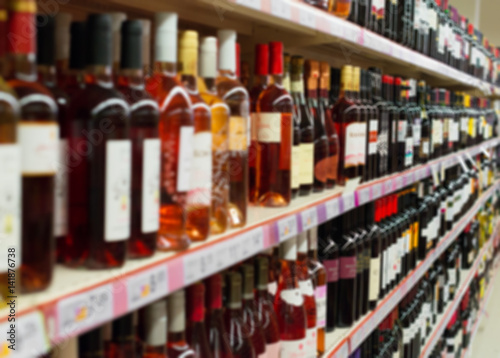 Cuadros en Lienzo Blurred image of shelves with alcoholic drinks in supermarket.