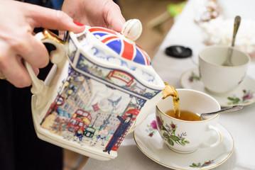 Tea poured into tea cup with British symbols