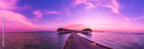 Obraz Sunset on Maldives island, water villas resort. Beautiful sky and clouds. Beautiful beach background for summer travel with sun, beach wooden jetty. Summer mood sun beach background concept. - fototapety do salonu