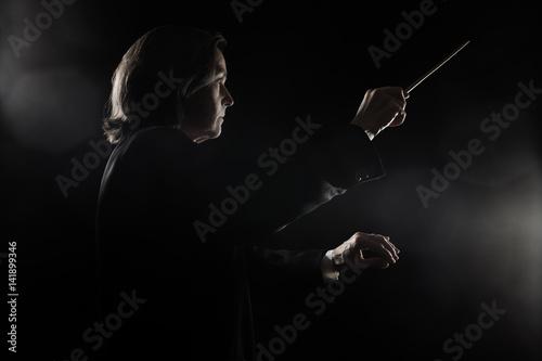 Orchestra conductor music conducting with baton Maestro
