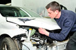 Mechanic inspecting car body damage at auto repair shop service station.