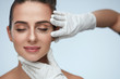Leinwandbild Motiv Closeup Of Beautician Hands Touching Young Female Patient Face