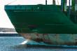 Green cargo ship's bow close up in still water, Riga