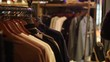 Choice of fashion clothes jackets hanging on wooden hangers at store shop. Person hands selecting clothes
