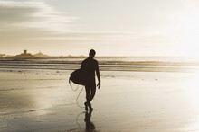 Silhouette Man Carrying Surfboard While Walking At Beach During Sunset