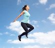happy smiling sporty young woman jumping in sky
