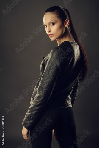 Photo  Beautiful girl in black leather jacket and black leggings posing on a gray background