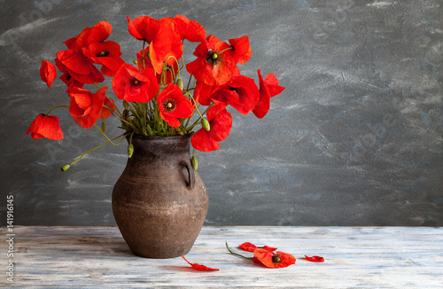 Still life in a rustic style: an old crock and a bouquet of red poppies on a wooden table
