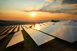 Photovoltaic panels of solar power station in the landscape at sunset. View from above.