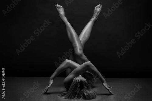 Obraz Athletic Naked woman body on black background. Fine art photo of female body.  - fototapety do salonu