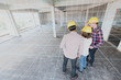 Three construction engineer discuss inside building, plan for renovation with 3d digital layout