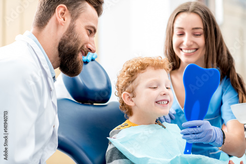 mata magnetyczna Young boy looking at the mirror with toothy smile sitting on the chair with dentist and assistant at the dental office
