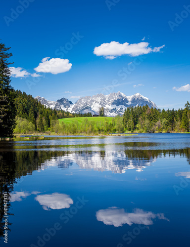 Foto auf Gartenposter Reflexion Snowy mountain range and clouds are reflected in a small lake near Kitzbuehel, Tyrol, Austria