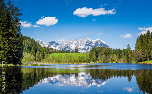 Tuinposter Reflectie Snowy mountain range is reflected in a small lake near Kitzbuehel, Tyrol, Austria