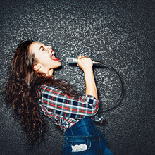 Karaoke Party. Time To Sing! Crazy Casual Curly Chic Girl Singing With Microphone. Studio Shot