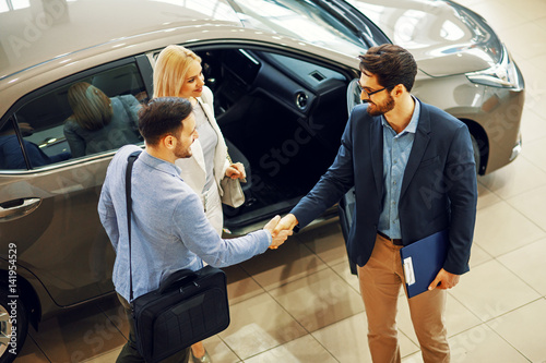 Fotografía Young couple shaking hands with sales agent after a successful car buying
