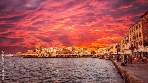 Foto op Plexiglas Crimson CHANIA, CRETE ISLAND, GREECE - JUNE 28, 2016: Sunset view of the old venetian port of Chania on Crete island Greece. Tourists relaxing on promenade.