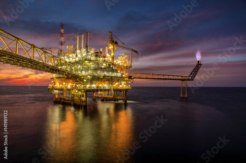 Fototapeta Offshore oil and rig platform in sunset or sunrise time. Construction of production process in the sea. obraz