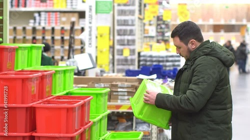 20s people buy green box in male. Youth adult boy in store. House hold goods. Guy chooses a box to buy. The buyer holds the object in hand. Male in mall 4k. Preparation for relocation.