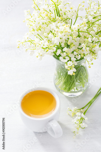 Poster Muguet de mai Cup of tea and bouquet of Lilies of the Valley in glass vase on rustic table.