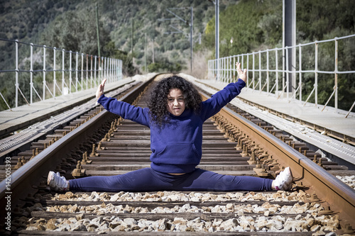 Poster Gymnastiek Haciendo gimnasia en las vías del tren. Niña jugando feliz en las vías del tren.