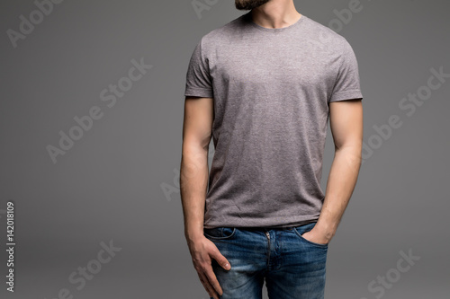 Photo  A man in a grey t-shirt and denims holds his hands in pockets.