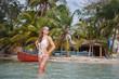 девушка в воде на фоне пляжа и лодки