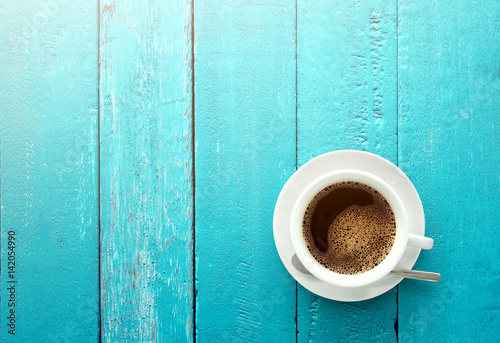 Top view of coffee cup on a ocean blue wood table background with copy space summer time concept