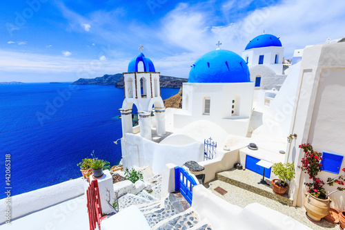 La pose en embrasure Santorini Santorini, Greece. Blue dome churches of Oia (Ia) village.