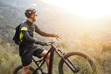 Side View Of Young Stylish Male Biker In Black Sportswear Standing On Top Of Hill With His Electric Two-wheeled Vehicle Admiring Beautiful Sunset While Cycling High In Mountains. Flare Sun Effect