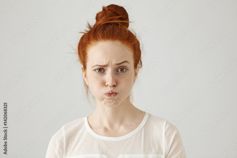 Fototapety, obrazy: Headshot of attractive funny young female with ginger hair dressed in white blouse feeling displeased or uncomfortable with something, blowing cheeks and frowning. Human face expressions and emotions