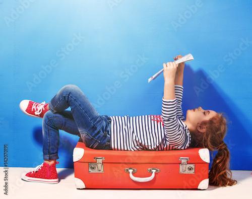dziewczynka-lezaca-na-walizce-na-tle-niebieskiej-sciany