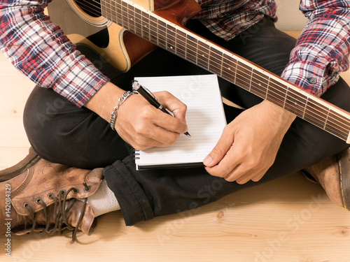 Photo Young hipster composing the song with guitar .