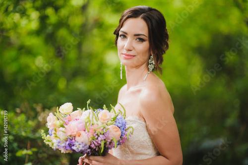 Half-length portrait of a beautiful bride in park Fototapet