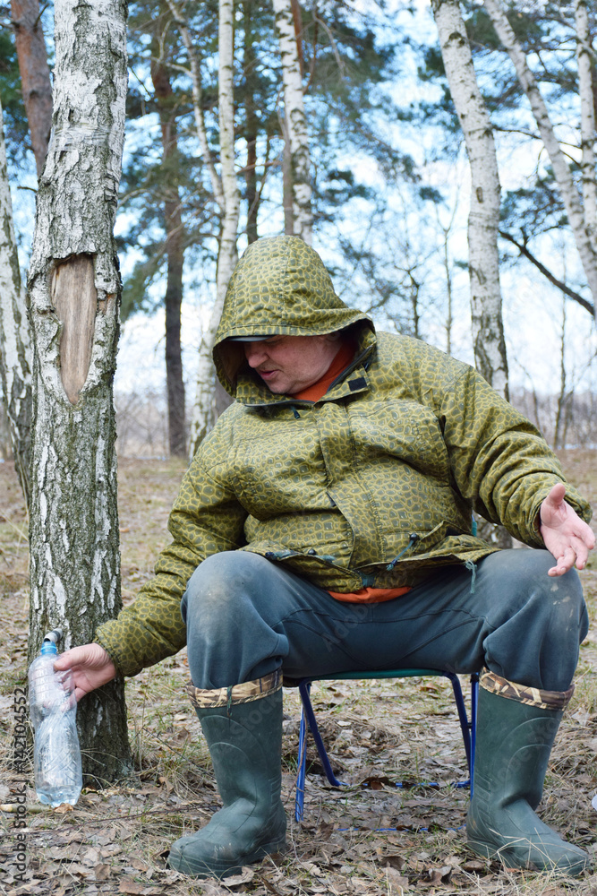 Valokuva  Mature caucasian man collecting birch juice