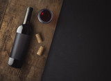 Bottle of red wine with label on old board. Glass of wine and cork. Wine bottle mockup. Top view. - 142117769