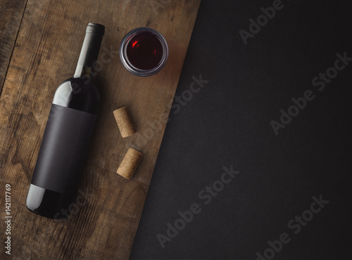 Foto  Bottle of red wine with label on old board