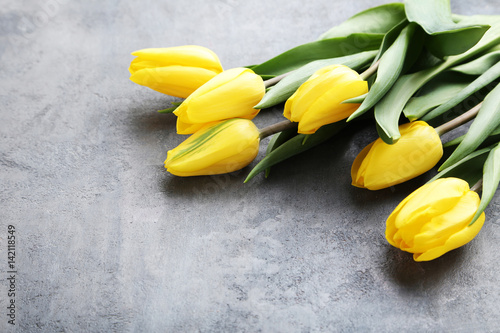 Bouquet of yellow tulips on grey wooden table