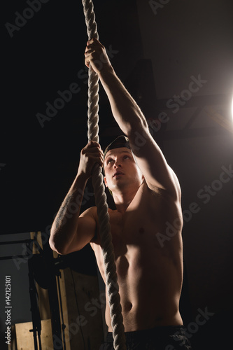 rope climb exercise man workout at gym climbing buy this stock