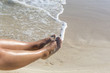 Woman's sexy feet against the turquoise water on the beach. Vacation and relaxation on the shore.