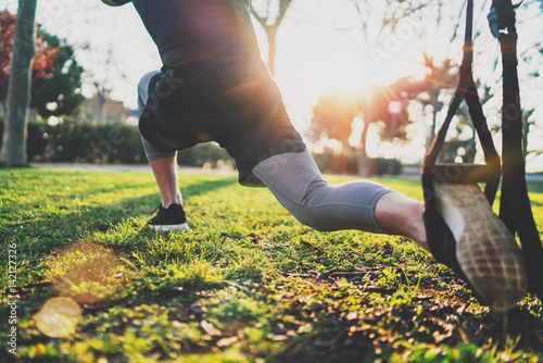 Feel your strength concept.Young athlete exercising trx outside in sunny park.Great TRX workout.Handsome man in sportswear doing exercising outdoors.Blurred background,flare.