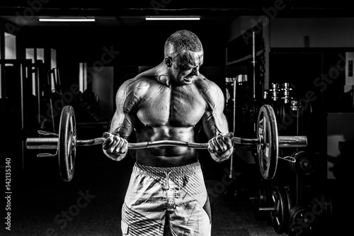Fotografija  Muscular bodybuilder guy doing exercises on biceps with big dumbbell in gym