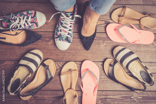 Fotografia  Collection of female shoes on wooden floor. Fashion background