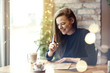 Beautiful young woman laugh drinking coffee in cafe restaurant, portrait of laughing happy lady near window. Vocation holidays evening concept