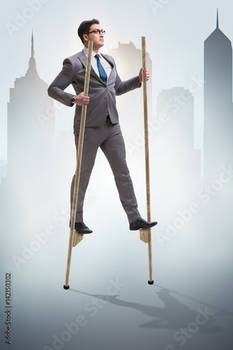 Valokuva Businessman walking on stilts - standing out from the crowd