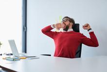 Portrait Of Sleepy Man Yawning In Office
