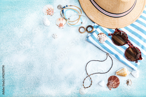 Fototapeta top view of straw hat, sunglasses and striped clothes on blue tabletop with white sand. Summer holidays concept obraz na płótnie