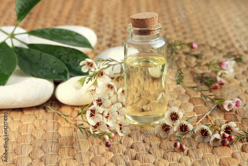 Fotografie, Obraz  Bottle of essential aroma oil with flowers and stones on straw mat